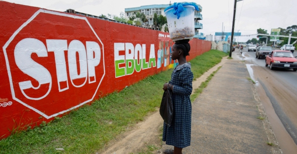 A woman looks at an Ebola sensitization mural in Monrovia, Liberia. (Photo: Ahmed Jallanzo/EPA/Newscom)