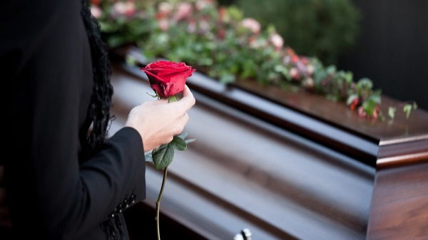 person-holding-rose-by-coffin